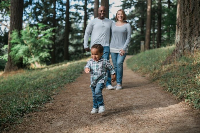 A young boy is walking down a forest path, his mother and father are cheering him on.