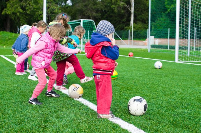 A group of toddlers on a football field, they are learning how to kick a ball