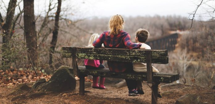 A woman is talking with her two children, they are sitting on a bench in a forest