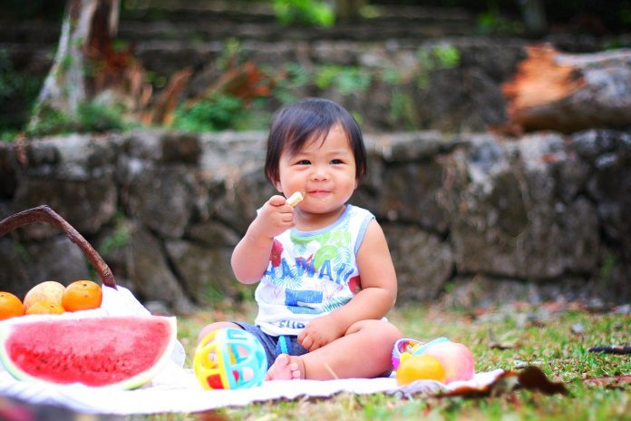 Happy young child on a picnic, surrounded by fruit