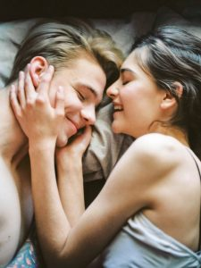 Two people laughing in bed