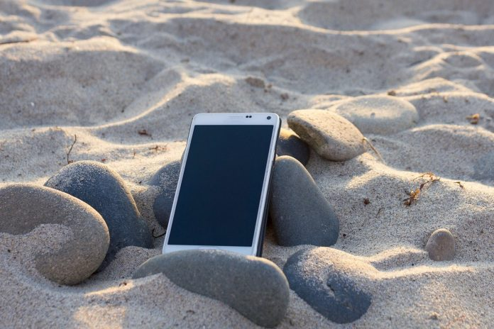 A smartphone is turned off and left on some rocks on a sunny beach