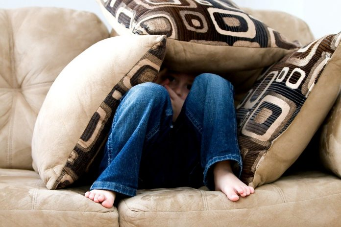 A boy is huddled on a couch, hiding under pillows.