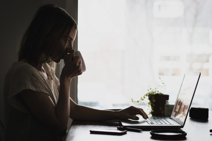 A woman is sitting at her desk and drinking coffee. The big window next to her shows bleak weather.