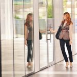 A woman, dressed for work, is hesitating in front of a glass door that shows her reflection.