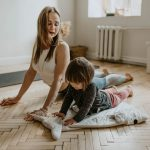 A woman stretching with her daughter