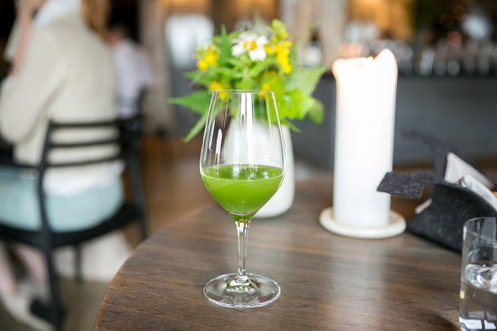 green cucumber juice in a wine glass