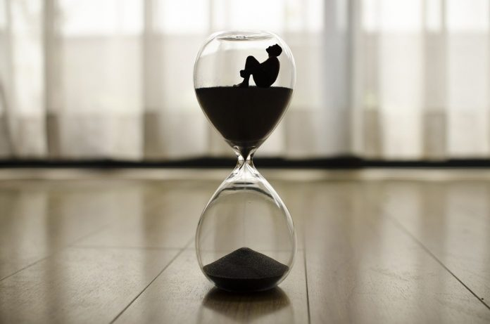 An illustration with a person trapped inside an hourglass.